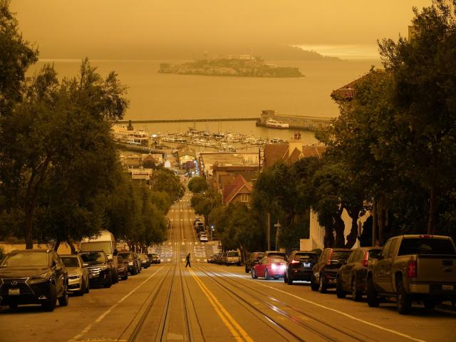 Người đàn ông băng qua phố Hyde dưới bầu trời màu cam đục do khói lửa