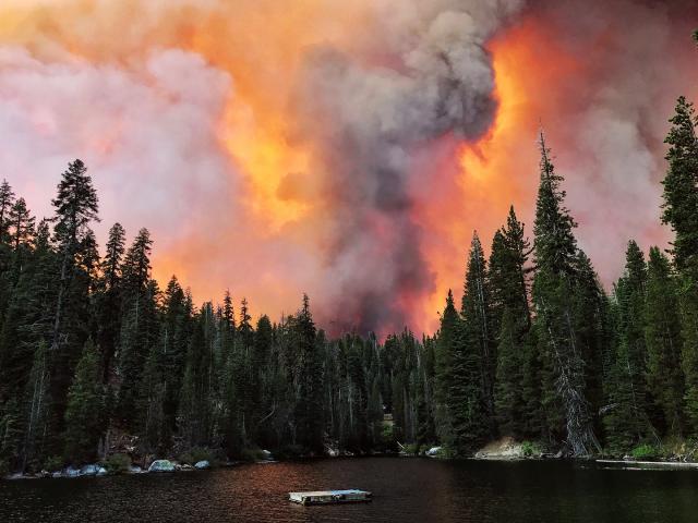 Khói từ đám cháy cuồn cuộn vượt qua một sườn núi và được nhìn thấy từ Hồ Huntington