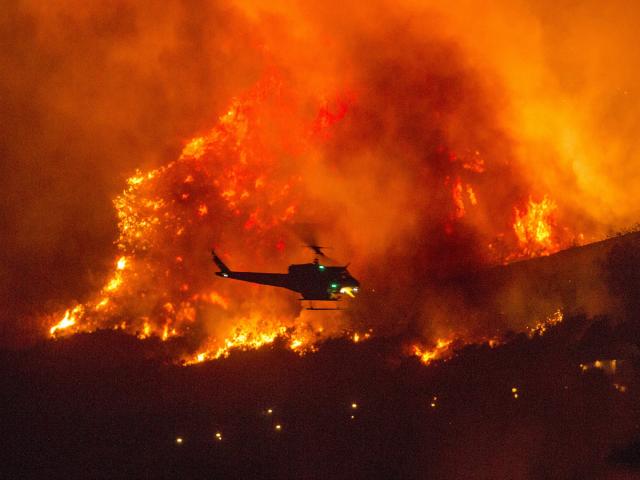 Một chiếc trực thăng chuẩn bị đổ nước xuống đám cháy