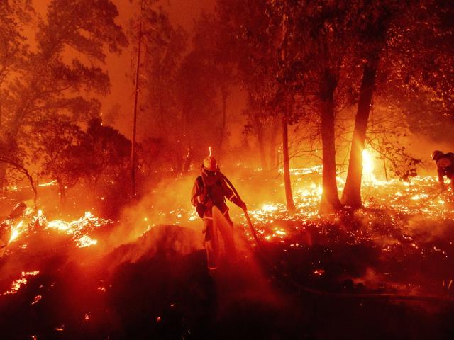 Lính cứu hỏa đang vật lộn với ngọn lửa khi nó đe dọa những ngôi nhà trong khu vực Cascadel Woods của Hạt Madera, California