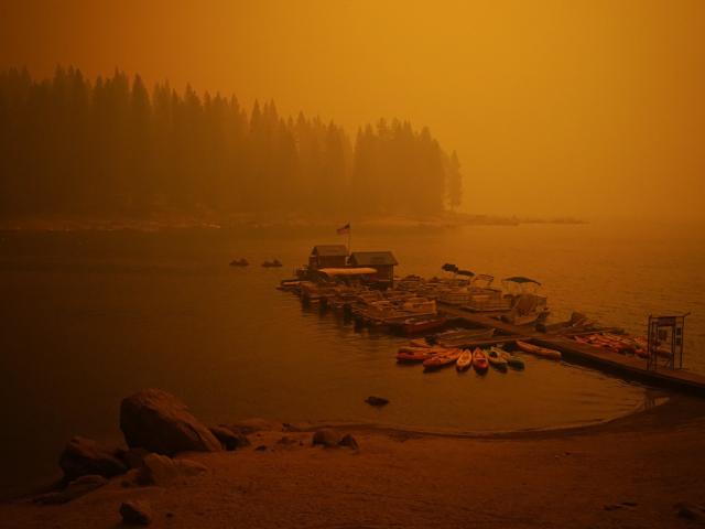 Khói từ đám cháy rừng bao trùm bầu trời trên một bến thuyền