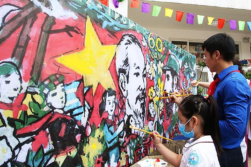 """Đại diện lãnh đạo các bộ, ngành cùng thiếu nhi cùng vẽ bức tranh khổ lớn """"Việt Nam - Cuba thắm tình đoàn kết"""" tại Lễ phát động."""
