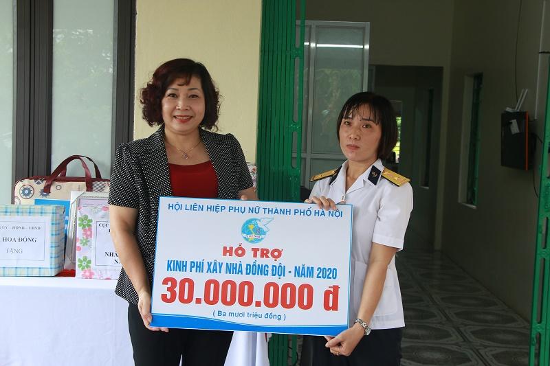 Đồng chí Lê Thị Thiên Hương, Phó Chủ tịch Hội LHPN Hà Nội trao biển tượng trưng kinh phí hỗ trợ xây nhà cho trung úy Bùi Thị Hiền.