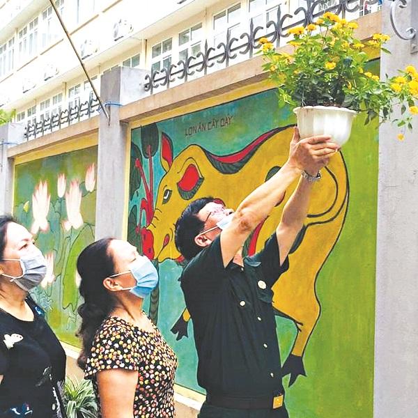 Chị em cán bộ hội, Hội Cựu chiến binh tham gia treo các giỏ hoa lên trên các bức tường bích họa tại Ngõ Quỳnh