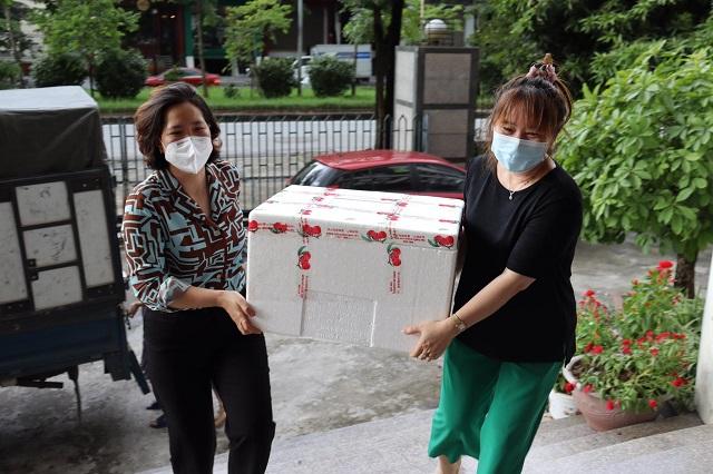 Với số lượng lớn, Chủ tịch Hội LHPN Hà Nội Lê Kim Anh (áo xanh) cũng chung tay dỡ các thùng vải thiều từ trên xe xuống, sẵn sàng để các đơn vị đến tiếp nhận.