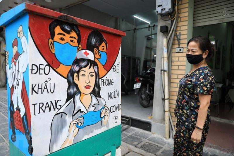 Người dân xem những bức tranh về phòng chống dịch trên các bôt điện Ảnh  Thành Đạt TTXVN
