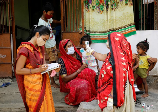 Một nhân viên y tế kiểm tra nhiệt độ của người dân trong làng ở ngoại ô Ahmedabad, Ấn Độ.
