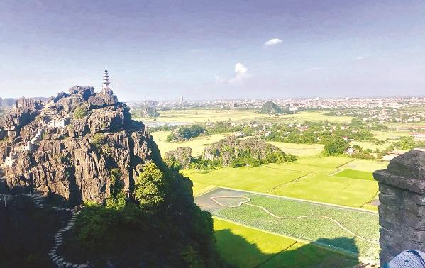 Từ đỉnh núi Ngoạ Long, du khách có thể chiêm ngưỡng cánh đồng lúa chín vàng và đầm sen với cây cầu hình trái tim