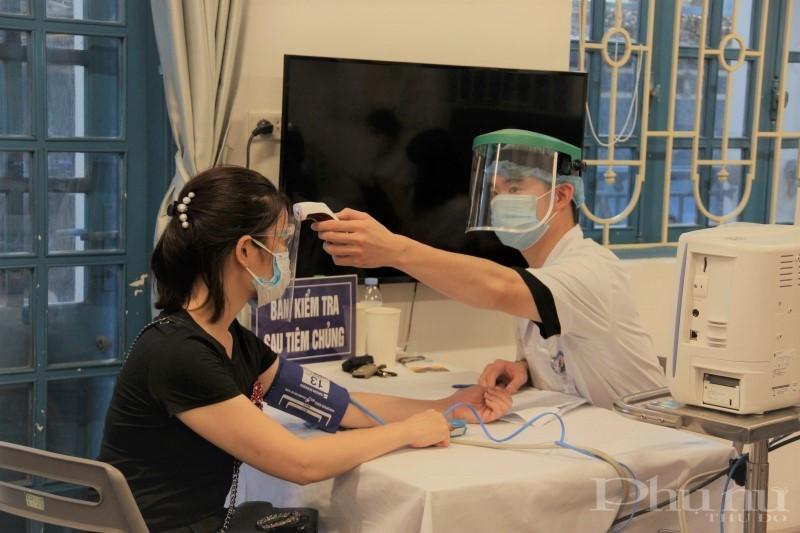 Sau tiêm, người dân được hướng dẫn ngồi chờ 30 phút để theo dõi các phản ứng phụ; sau đó được bác sĩ kiểm tra huyết áp để đảm bảo sức khỏe người tiêm ổn định trước khi về nhà.