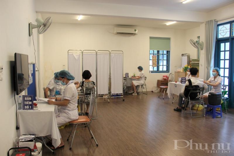 Điểm tiêm tại phường Định Công hiện có 3 dây chuyền tiêm, giữa các bàn tiêm đều tuân thủ quy định giãn cách để phòng dịch Covid-19.