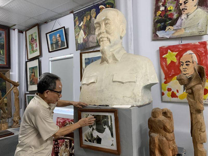 Họa sỹ Lê Duy Ứng bên bức tranh vẽ Bác Hồ bằng máu treo trong bảo tàng riêng của nhà mình