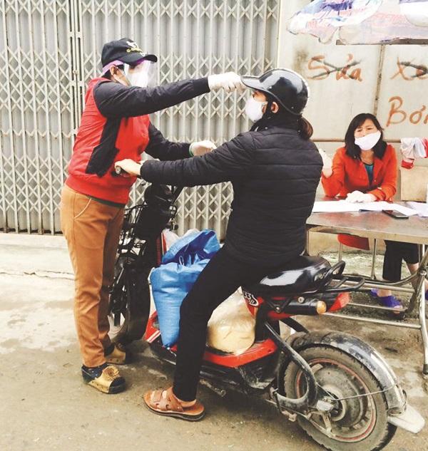 Chị Hà Thị Lân đang làm nhiệm vụ tại chốt kiểm soát y tế của Tổ dân phố 1