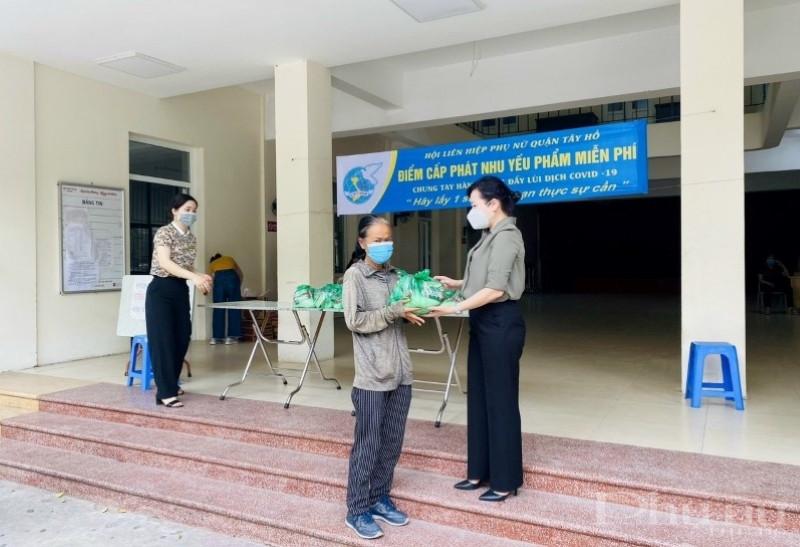 Chị Bùi Thị Ngọc Thúy - Chủ tịch Hội LHPN quận Tây Hồ tặng nhu yếu phẩm cho hộ dân khó khăn trên địa bàn.