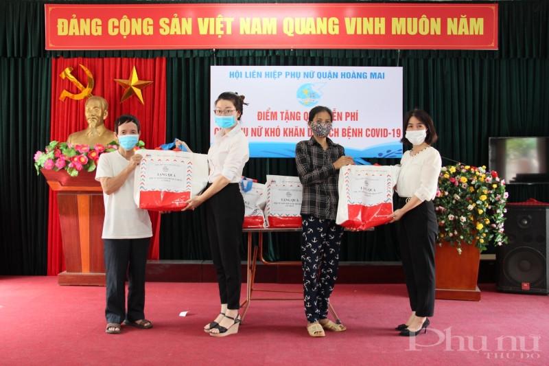 Chị Nguyễn Lệ Hằng - Chủ tịch Hội LHPN quận Hoàng Mai (ngoài cùng bên phải) và chị Nguyễn Mai Anh - Phó Chủ tịch Hội LHPN quận Hoàng Mai (thứ 2 từ trái) tặng quà cho gia đình hội viên phụ nữ khó khăn phường Vĩnh Tuy.