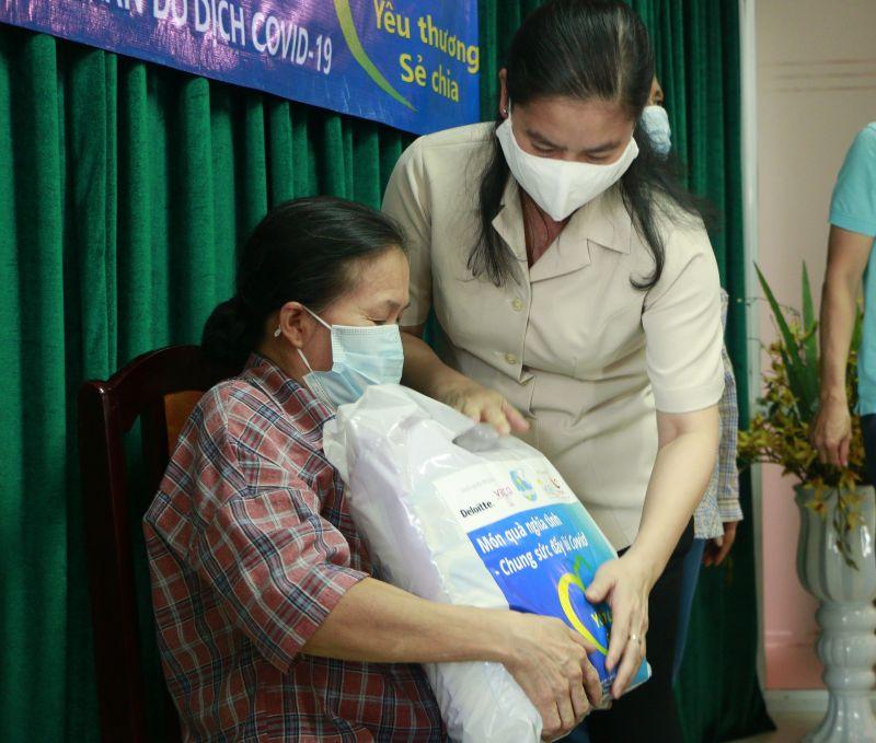 Đồng chí Bùi Thị Thu Thảo, Phó Chủ tịch Trung ương Hội LHPN Việt Nam trao quà cho một phụ nữ khó khăn ở quận Cầu Giấy tại buổi tiếp nhận