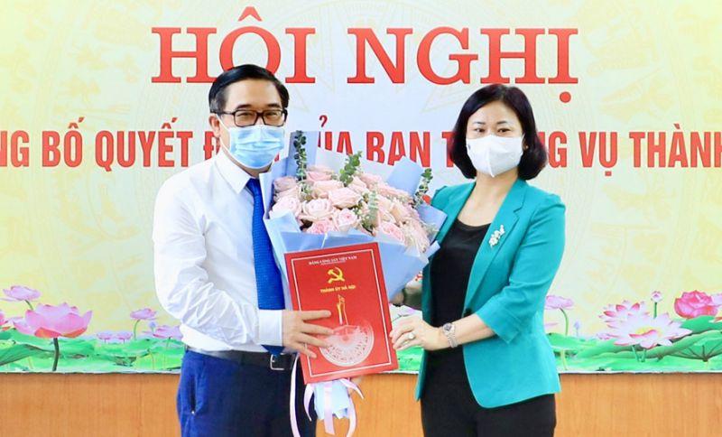 Phó Bí thư Thường trực Thành ủy Hà Nội Nguyễn Thị Tuyến trao Quyết định của Ban Thường vụ Thành ủy và tặng hoa chúc mừng đồng chí Đỗ Đình Hồng.