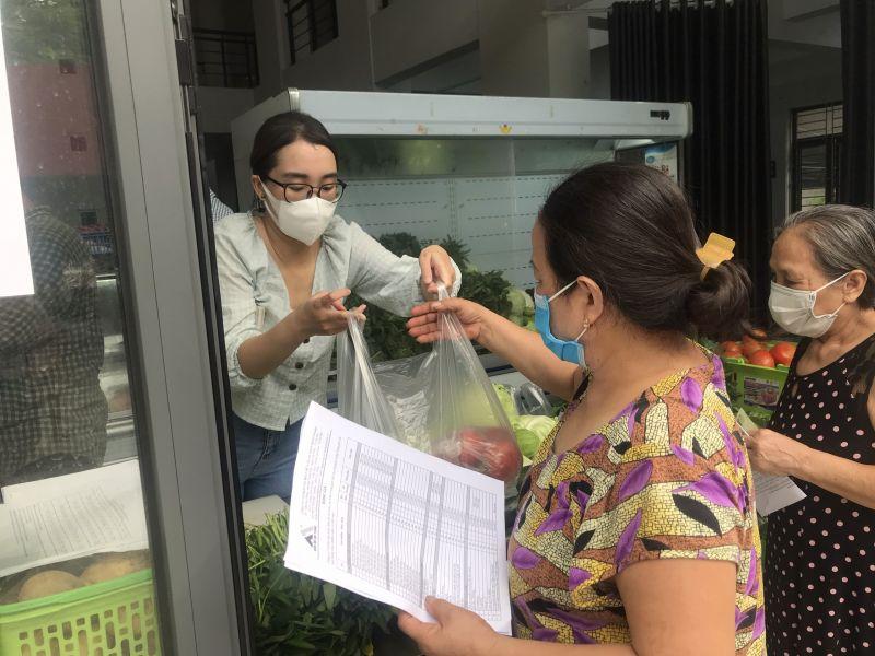 Người dân mua thực phẩm tại điểm bán hàng trong Nhà văn hoá phường Nhật Tân