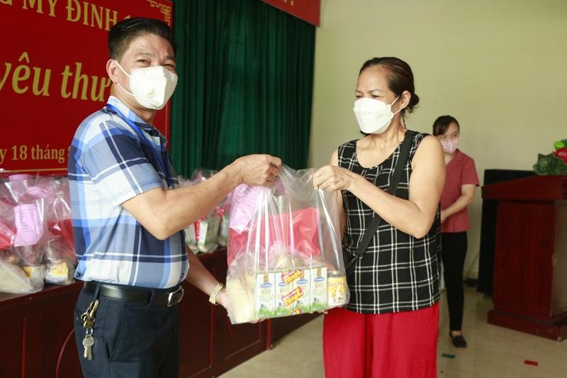 Đồng chí Trịnh Văn Quế, Chủ tịch UBND phường Mỹ Đình I trao quà hỗ trợ trẻ em bị ảnh hưởng bởi dịch qua người thân của trẻ.
