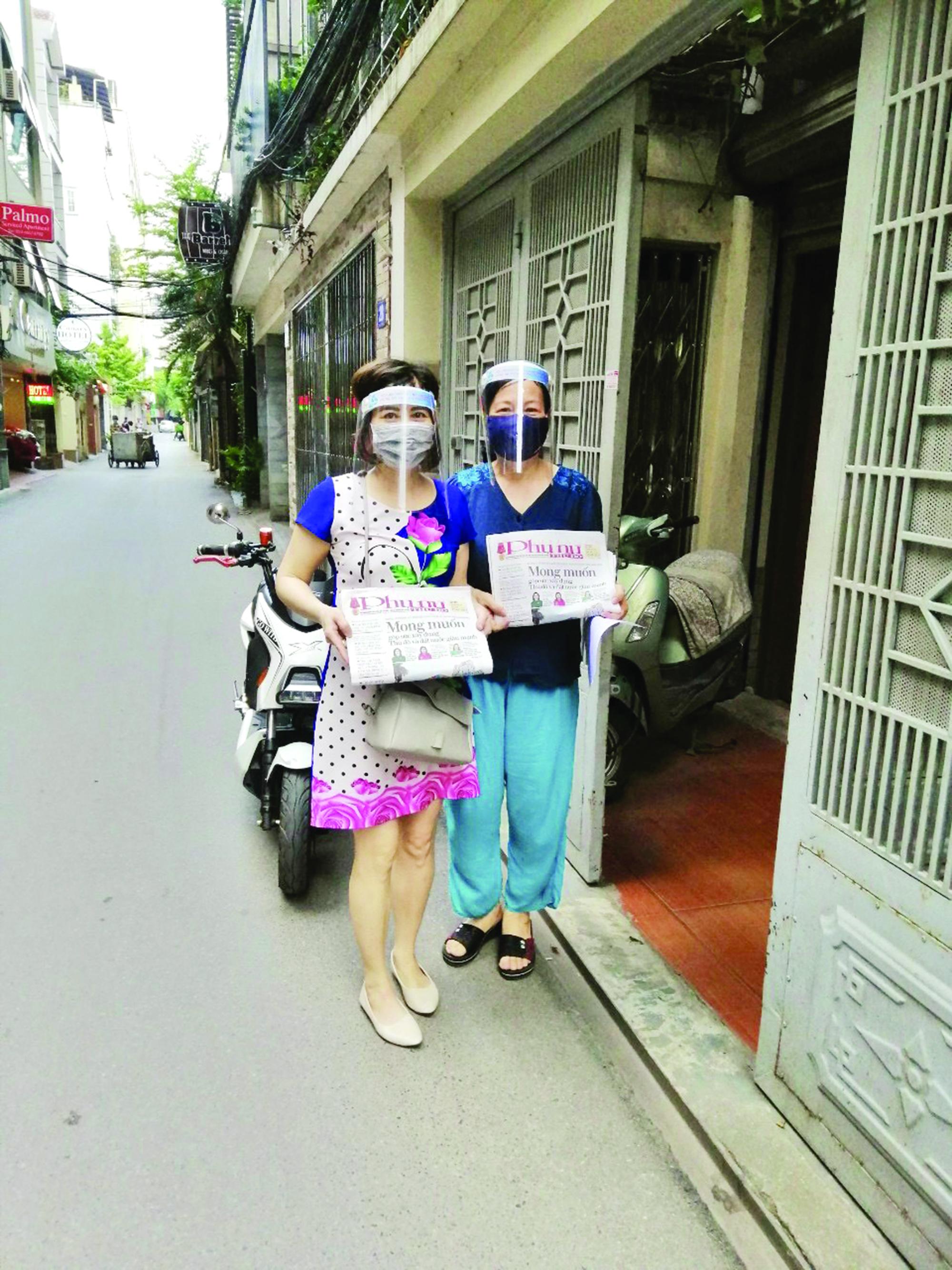 Cán bộ hội PN phường Liễu Giai đeo khẩu trang, đội mũ chắn giọt bắn chuyển báo Hội tới gia đình hội viên.