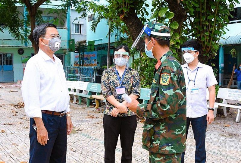 Đại diện cán bộ UBND Phường 1, quận Tân Bình trao đổi công việc với chỉ huy của nhóm chiến sĩ giúp dân tại địa phương.