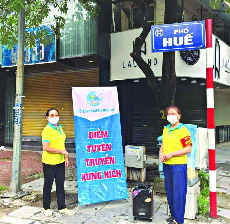 Cán bộ, hội viên phụ nữ phường Hàng Bài, quận Hoàn Kiếm tổ chức điểm tuyên truyền xung kích tại ngã tư Phố Huế 9 (trong đợt thực hiện giãn cách xã hội tháng 8).