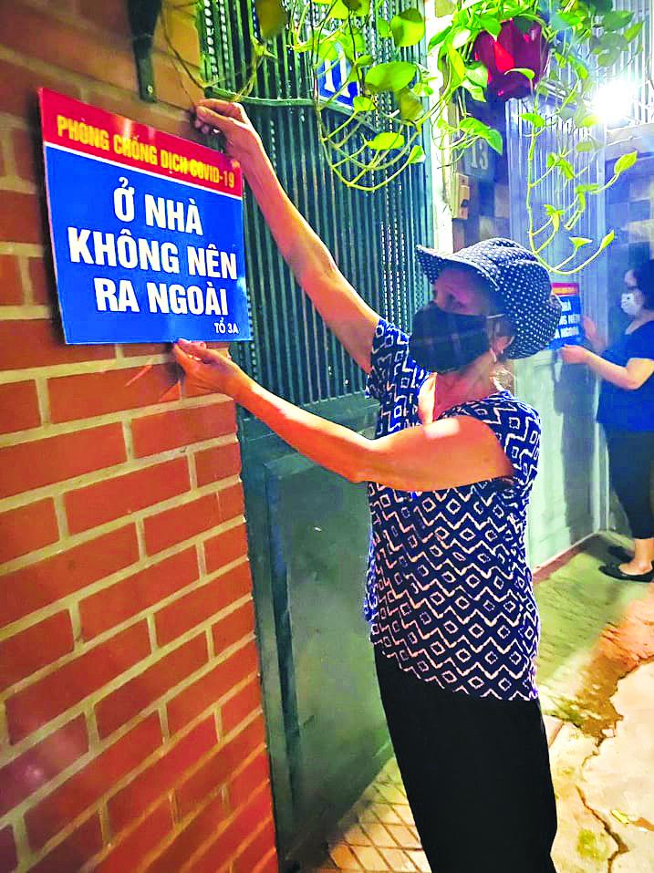 """Hội viên phụ nữ phường Liễu Giai, quận Ba Đình treo biển tuyên truyền """"Ở nhà không nên ra ngoài"""