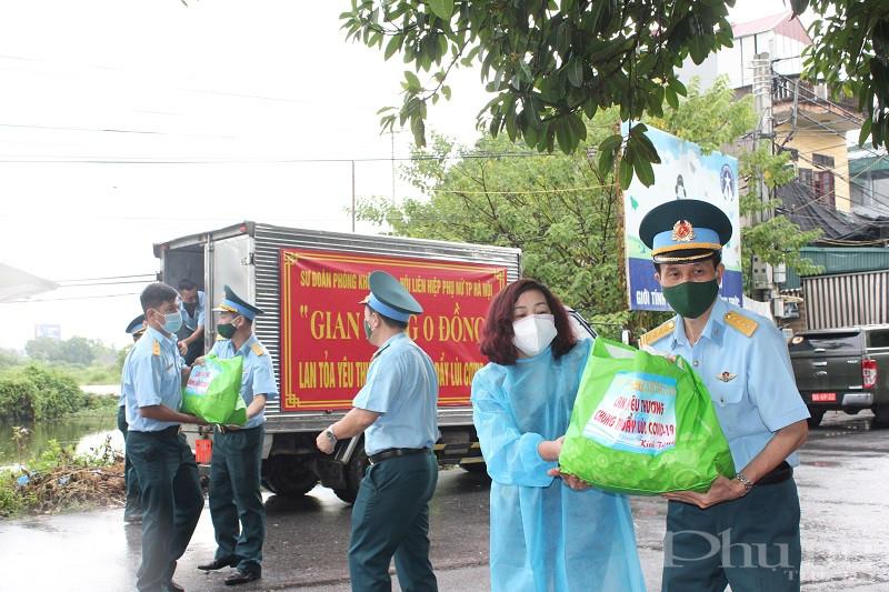 Các thành viên trong đoàn công tác chuyển các phần quà tới điểm chốt trực tại thôn Phương Nhị xã Liên Ninh