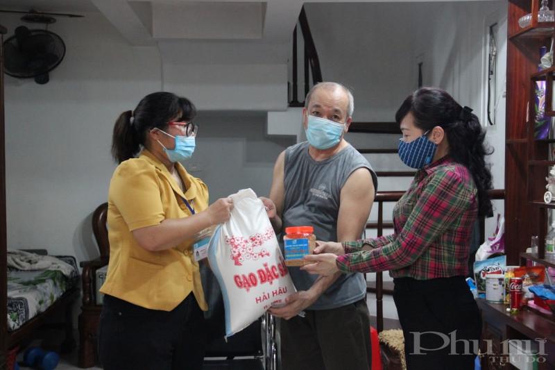 Chị Bùi Thị Ngọc Thúy (bên phải) và Phương Thúy Hằng (bên trái) tặng gạo và muối vừng cho một gia đình hội viên phụ nữ tại Chi hội số 14, Hội LHPN phường Bưởi.