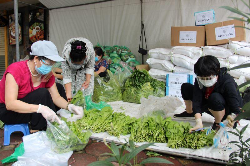 Cán bộ, hội viên phụ nữ phường Kim Đồng chia rau vào từng túi nhỏ để tặng người dân trong khu phong tỏa.
