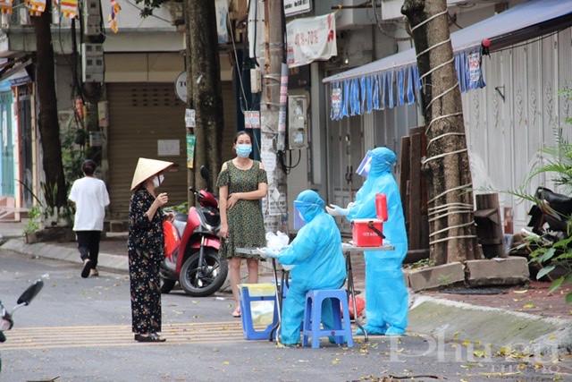 Cán bộ y tế lấy mẫu xét nghiệm cho người dân trong khu cách ly tại ngõ 24 Kim Đồng, phường Giáp Bát, Hoàng Mai, Hà Nội.
