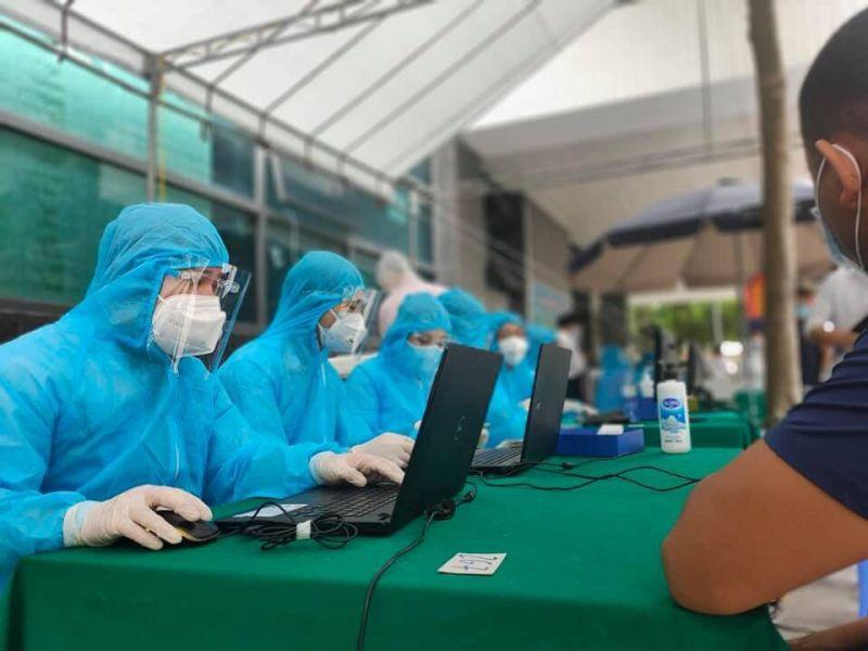 Cán bộ y tế lấy thông tin cá nhân người dân đến tiêm chủng phòng Covid-19