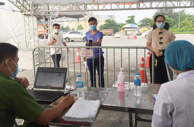Người dân quét mã QR Code khi đi qua chốt kiểm soát phòng dịch Covid-19 của thành phố