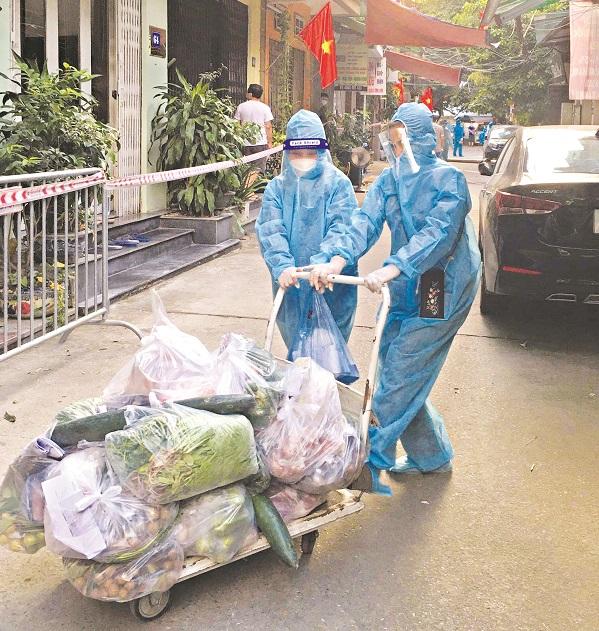 Các chị em phụ nữ phường Thanh Xuân Trung mặc đồ bảo hộ, đi chợ hộ và đưa đồ ăn cho các hộ dân trong thời gian cách ly tại phường (Ảnh: Hồng Nhung)