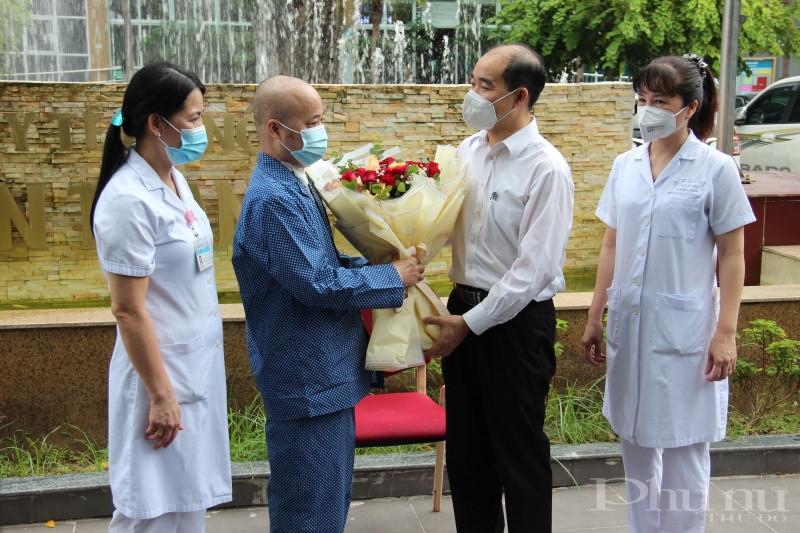 Lãnh đạo Sở Y tế Hà Nội và bệnh viện Đa khoa Thanh Nhàn tặng hoa chúc mừng bệnh nhân xuất viện.