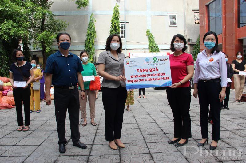 Chủ tịch Hội LHPN Hà Nội Lê Kim Anh (thứ 2 từ trái qua) và chị Yến - Phụ trách dự án Viện LIGHT thông qua Hội LHPN phường trao quà cho các nữ lao động di cư khó khăn.