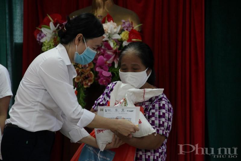 Chị Nguyễn Hoàng Yến, phụ trách dự án của Viện LIGHT trao quà cho một phụ nữ di cư có hoàn cảnh khó khăn của quận Ba Đình.