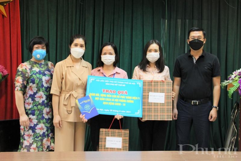 Phó Tổng biên tập Báo Phụ nữ Thủ đô Lê Thị Hồng Minh (thứ 2 từ trái qua) tặng quà cho chị Vũ Thị Dung.