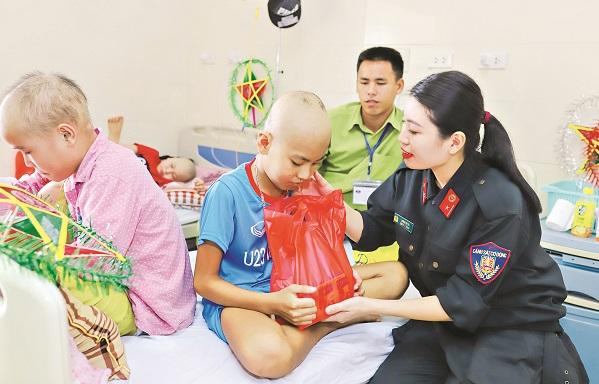 Trung úy Lương Thị Thu trao quà cho các cháu nhỏ bị bệnh ở  bệnh viện K