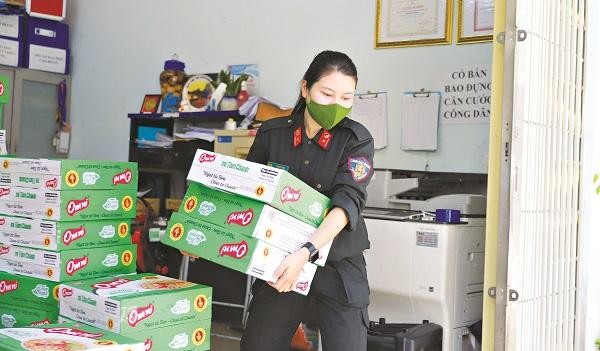 Trung úy Lương Thị Thu bê hàng chuẩn bị đi tặng cho bà con  khó khăn
