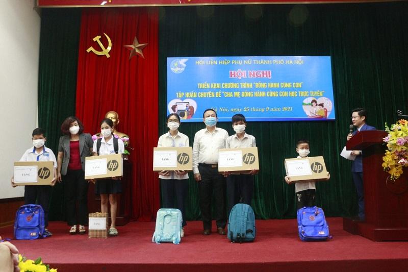 Đồng chí Lê Thị Thiên Hương, Phó Chủ tịch Hội LHPN Hà Nội và đồng chí Trịnh Huy Thành, Phó Trưởng ban Thường trực Ban Dân vận Thành ủy Hà Nội trao tặng máy tính cho các cháu học sinh khó khăn