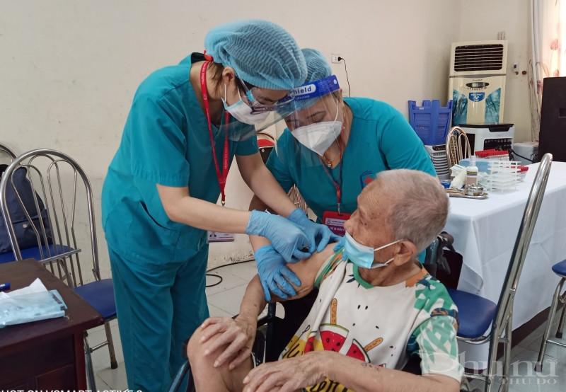 Bác sĩ tiêm chủng cho người cao tuổi tại hội bảo trợ.