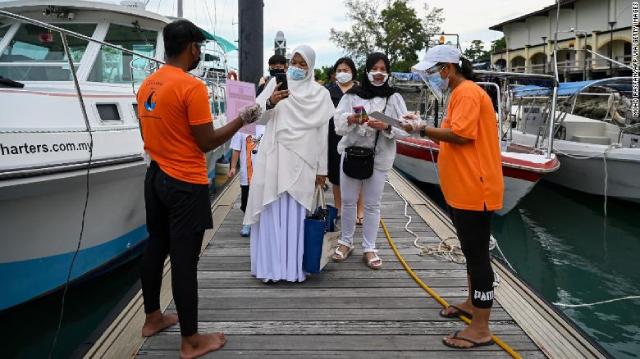 Hành khách quét mã ứng dụng để theo dõi tình trạng sức khỏe trước khi lên du thuyền ở Langkawi, Malaysia.