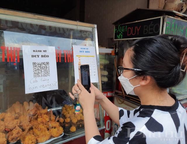 Một khách hàng đang thực hiện quét QR khai báo Y tế tại cửa hàng của cô Bằng.