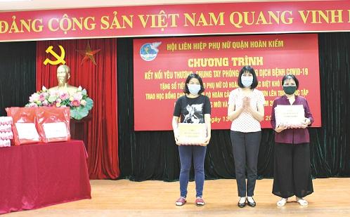 Đồng chí Trịnh Thị Huệ - Chủ tịch Hội LHPN quận Hoàn Kiếm tặng sổ tiết kiệm cho phụ nữ khó khăn.