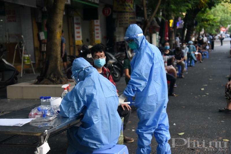 Nhân viên y tế lấy mẫu xét nghiệm cho đối tượng liên quan ca Covid-19 tại BV Việt Đức.